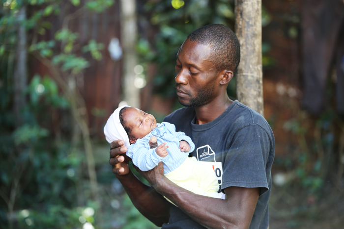 Dominican-Haitian man with baby in the Dominican Republic. Credit: MRG.