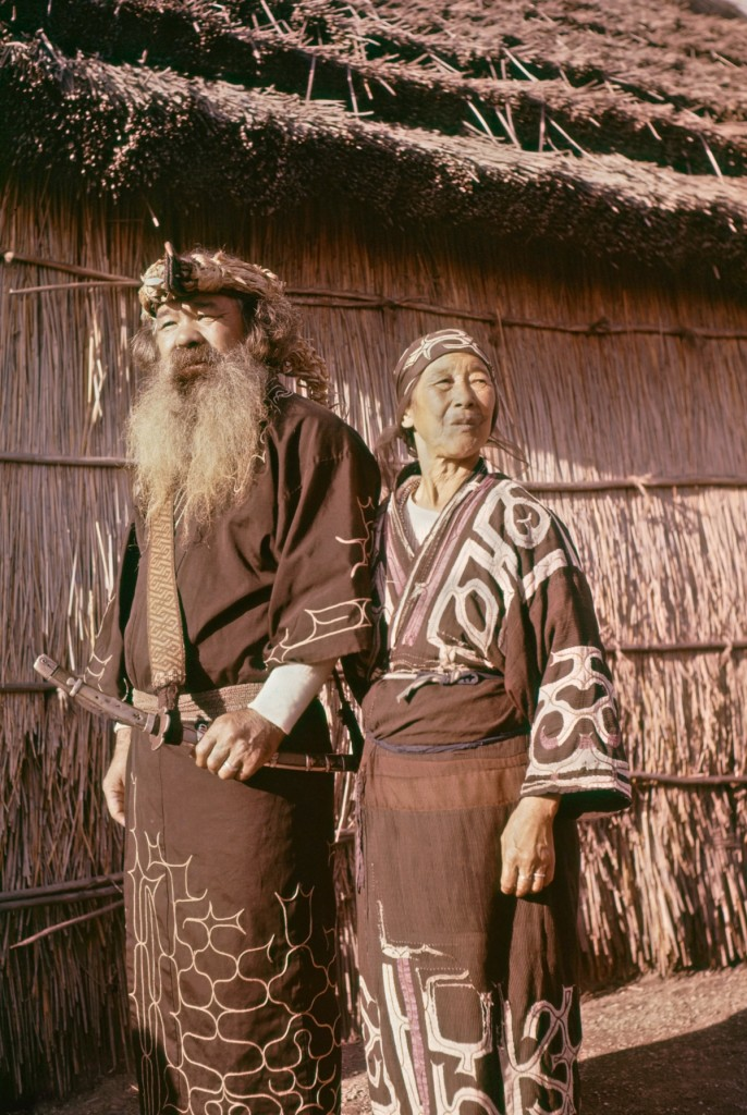 Shiroai, Hokkaido, Japan - Ainu man and woman outside in ceremonial attire for the Marimo festival in Shiroai, Hokkaido, Japan. October 8, 1961, Archival photo.